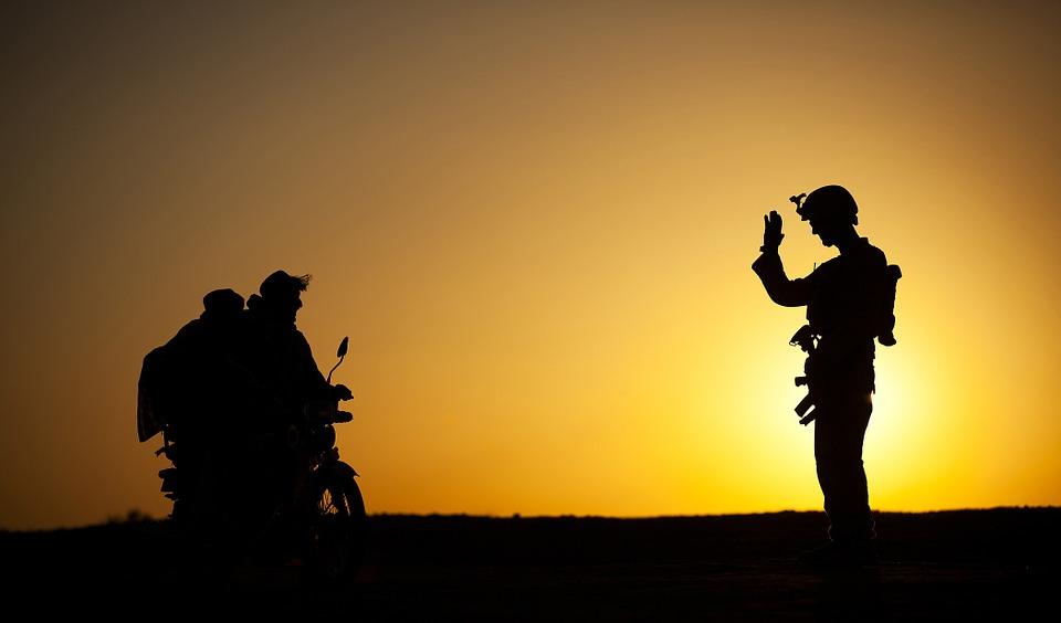 兵士が民間人に手を振って オートバイ シルエット 日没 フレンドリー 自転車 道路 車両